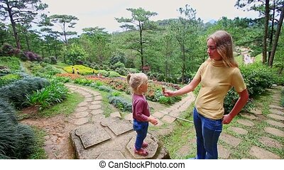 Mother Gives Little Girl Ice Cream Tube on Stone Path in...