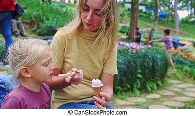Closeup Mother Feeds with Spoon Little Girl against Flowers...