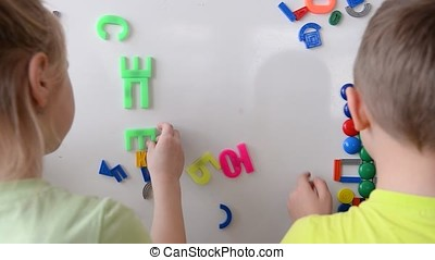 Children playing with magnetic drawing board and alphabet