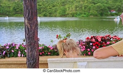 Blond Mother Little Girl Sit on Bench Watch Lake Backside -...