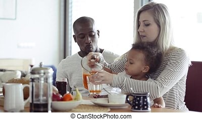 Young interracial family with little children having...