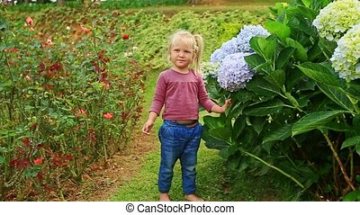 Closeup Little Girl Stands by Blue Hydrangea Flowers in Park