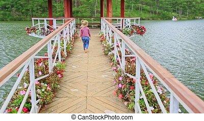 Little Girl Walks Barefoot on Bridge to Lake Pavilion in Park