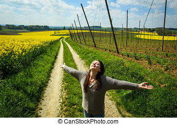 Fields of Bavaria - A woman spreading her arms standing on a...
