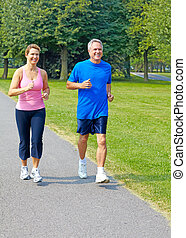 jogging - Happy elderly seniors couple jogging in park