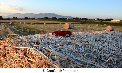 Toy car on a round bale - Toy car on a round straw bale