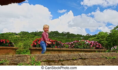 Little Blond Girl Stands on Slope Waves Hands Closeup