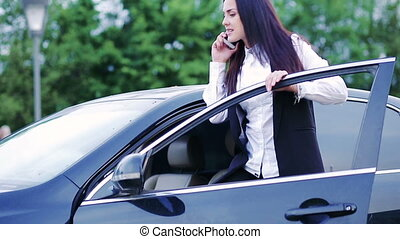 Businesswoman talking over a phone next to her car