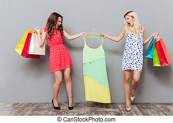 Women sharing dress - Two young angry women with packages...