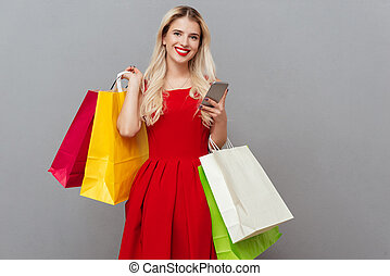 Woman looking camera with packages - Cheerful woman looking...