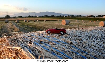 Toy car on a round straw bale at the sunset