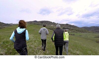Group of seniors running outside on the green hills.