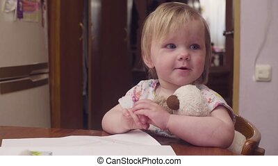 Little baby girl sitting at a table