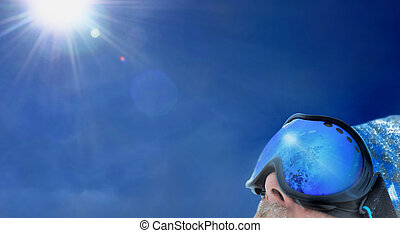 sun shining with a skier - mask wearing by a skier with sun...