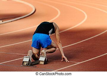 male runner starting blocks