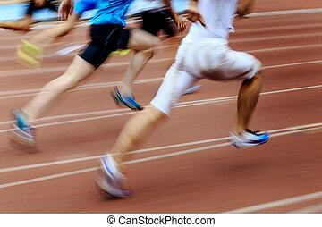blurred motion group runners sprinters running on track...
