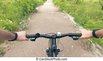 Trip to mountain bike from the first-person hand the wheel and road dust