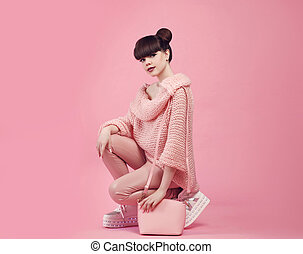 Fashion outfit style. Young stylish teen holding purse in boot shoes. Fashionable girl dressed wool jumper and leather pants posing over studio pink background.