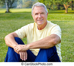 elderly man in park - Happy smiling elderly man in park