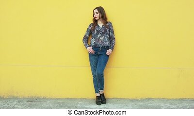 Street youth movements and styles. Beautiful girl in blue jeans against a bright orange wall.