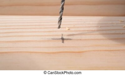 Drilling a hole in a pine wood plank with a drill bit