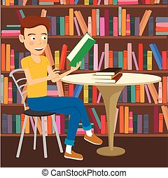 Male student reads textbook sitting at the table in college library