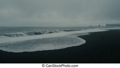 Aerial view of the beautiful black volcanic beach in...