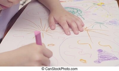 Hands of a little girl drawing at a table