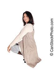 Woman crouching in deerskin coat. - A young Hispanic woman...