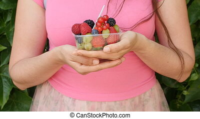 Woman holding berries and fruit in hands - Young Woman...