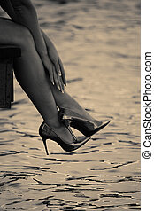 Elegant womans legs with shiny heels. Black and white photo.