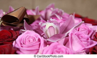 Red and pink roses with orchid flowers bouquet close up