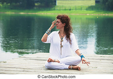 young woman practice yoga breathing techniques outdoor by...