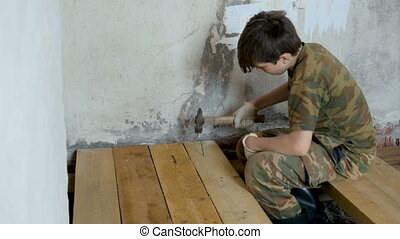 The teenager is hammering a nail into the board. - The...