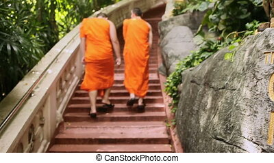 Two monks in orange robes walk up the stairs at Wat Saket...
