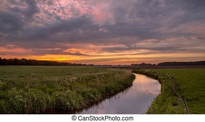 Sunrise timelapse over lowland river in flat countryside of the Netherlands