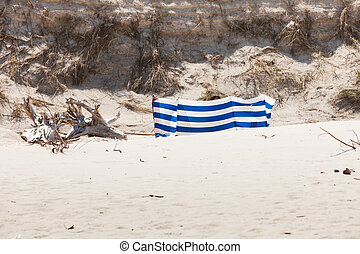 Blue and white windbreak on sandy beach. - Blue and white...