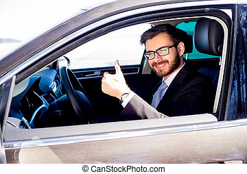 Happy man driving a car - Portrait of a handsome man driving...