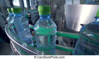 Bottles with drinking water on conveyor.