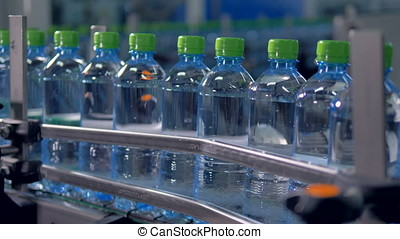 Line of full bottles pushed through a conveyor. - Slow...