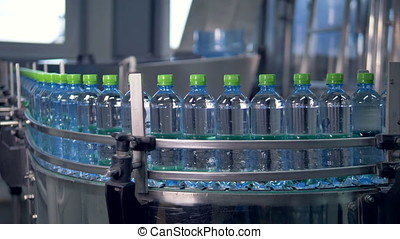 Focused curved line of filled drinking water bottles. - Long...