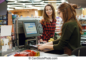Happy young lady standing in supermarket - Photo of happy...