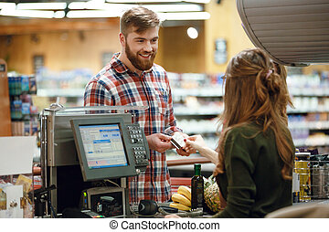 Happy young man standing in supermarket shop