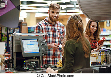 Cheerful young man standing in supermarket shop