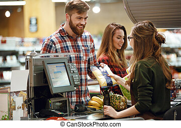 ?heerful young man standing in supermarket shop - Image of...