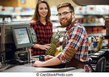 Cheerful cashier man on workspace in supermarket shop.