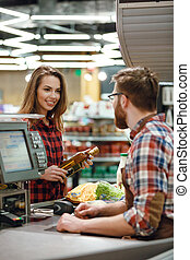 Happy young lady standing near cashier's desk - Photo of...