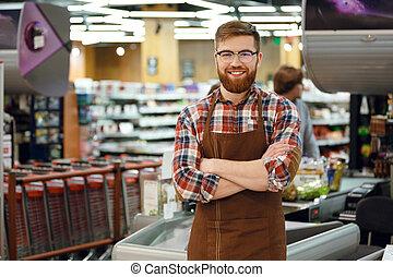 Cashier man on workspace in supermarket shop