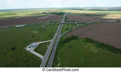 Aerial shot of a country highway with trucks and green agricultural fields nearby