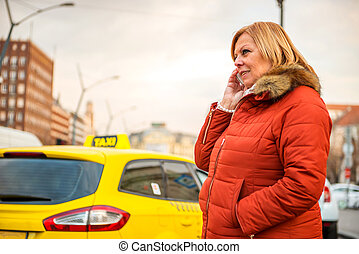 Nice woman on the street with a phone - A nice middle age...